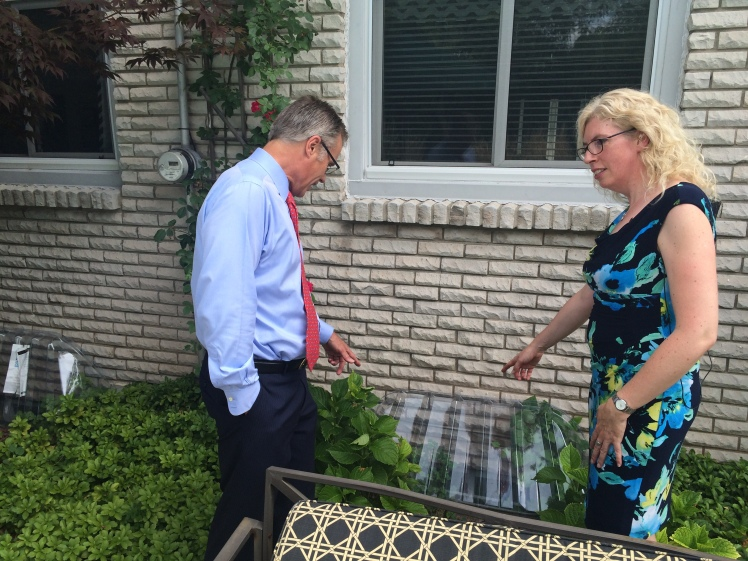Burlington Mayor Goldring and Cheryl Evans, Director of the Home Flood Protection Program point to a window well cover.